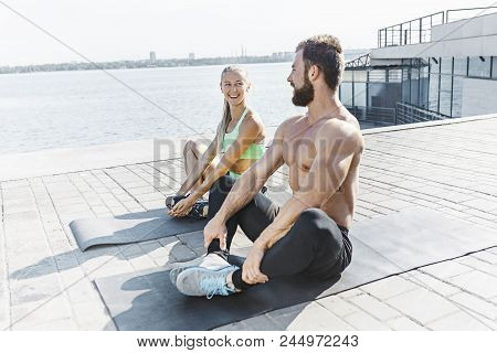 Fit fitness woman and man doing stretching exercises outdoors at city background. Couple doing hamstring leg exercise and stretches. Female amd male sports models exercising outdoor in summer at morning. poster