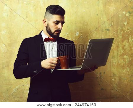 Project Manager With Serious Face Puts Coffee On Laptop. Bearded Project Manager With Serious Face E