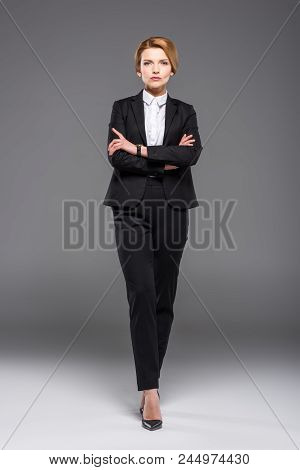 Confident Businesswoman Posing In Formal Wear With Crossed Arms, Isolated On Grey