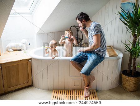 Father With Two Toddlers In The Bath Tub Brushing Teeth In The Bathroom At Home. Paternity Leave.
