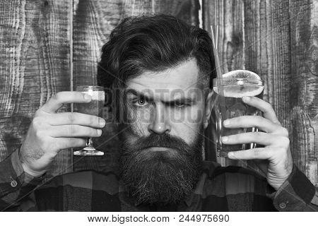Barman With Short Cocktail On Strict Face, Wooden Background. Portrait Of Handsome Bartender At Work