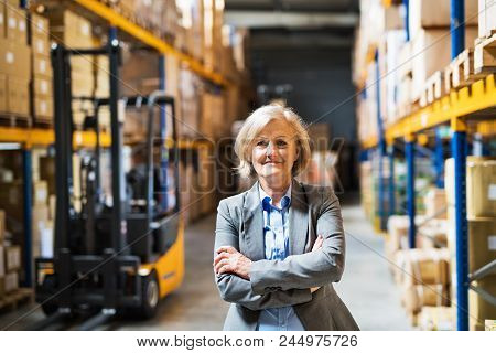 Portrait Of A Senior Woman Warehouse Manager Or Supervisor, Arms Crossed.
