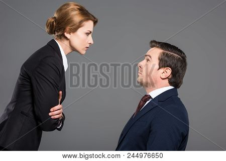 Angry Female Boss Looking At Scared Businessman, Isolated On Grey, Feminism Concept