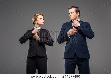 Serious Businesswoman And Businessman Fixing Ties And Looking At Each Other, Isolated On Grey, Femin