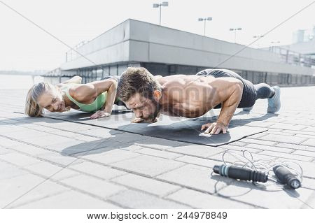 Fit Fitness Woman And Man Doing Fitness Exercises Outdoor At City Background. Couple Doing Hamstring