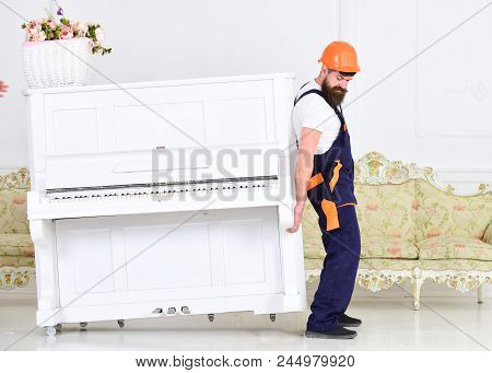 Loader Moves Piano Instrument. Heavy Loads Concept. Man With Beard Worker In Helmet And Overalls Lif