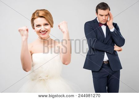 Excited Bride In Wedding Dress And Worried Groom Behind, Isolated On Grey, Feminism Concept
