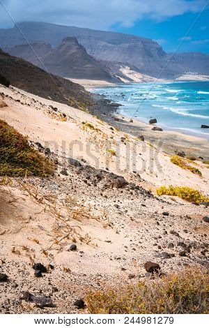 Stunning Desolate Landscape Of Sand Dunes And Desert Plants In Front Of Ocean Waves On Baia Das Gata