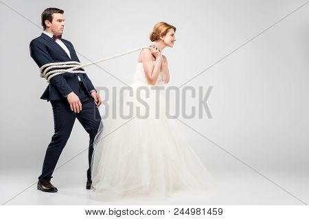 Bride In Wedding Dress Pulling Groom Bound With Rope, Isolated On Grey, Feminism Concept