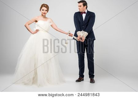 Attractive Bride In Wedding Dress And Groom Bound With Rope, Isolated On Grey, Feminism Concept