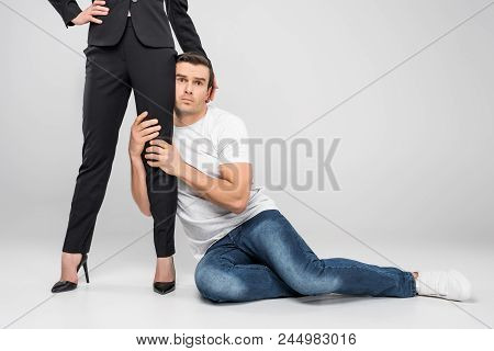 Frightened Husband Hugging Leg Of His Business Wife, Feminism Concept, Isolated On Grey