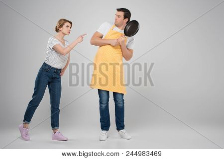 Angry Wife And Frightened Husband In Apron With Frying Pan, Feminism Concept, Isolated On Grey