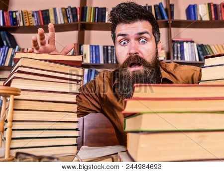 Man On Shocked Face Between Piles Of Books, While Studying In Library, Bookshelves On Background. Te