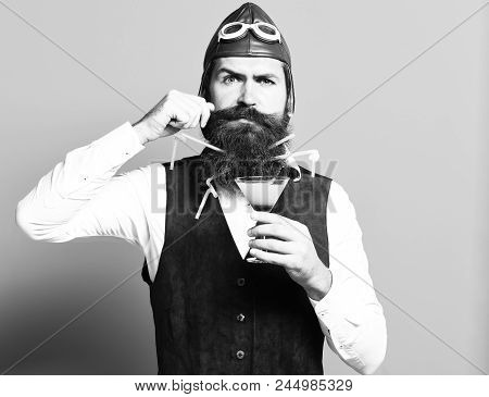 Handsome Bearded Pilot Or Aviator Man With Long Beard And Mustache On Serious Face Holding Glass Of