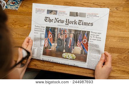 Paris, France - June 13, 2018: Woman Reading The New York Times Newspaper In The Office Showing On C