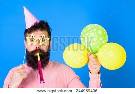 Man With Beard On Surprised Face Holds Air Balloons, Blue Background. Guy In Party Hat With Holiday