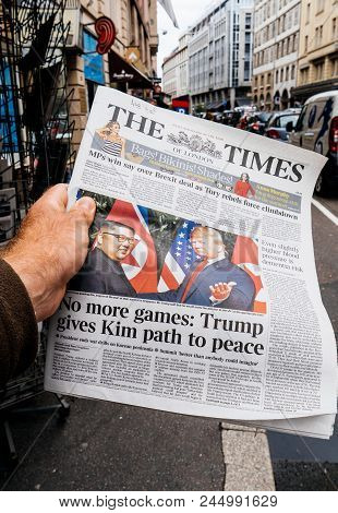 Paris, France - June 13, 2018: Man Buying The Times Newspaper At Press Kiosk Showing On Cover  U.s.
