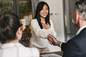 Business, career and placement concept - two business partners in office shaking hand of young asian woman after successful negotiations or interview poster