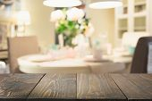 Blurred background. Modern defocused defocused kitchen or cafe with empty wooden tabletop and space for you design. poster