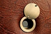 Peephole with an open damper on a brown leatherette door. poster