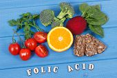 Inscription folic acid with nutritious products containing vitamin B9 and natural sources of minerals, concept of healthy nutrition poster