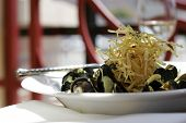 Steamed mussels topped with crispy shoestring potatoes poster