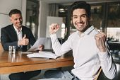 Career, office and placement concept - successful caucasian man 30s rejoicing and clenching fists during job interview with employee of big company poster