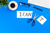 I can concept. Encourage youself. Sciccors cut off the letter t of written word I can't. Office desk. Blue background top view. poster
