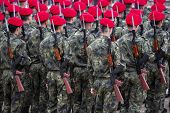 Troops with assault rifle and red hats from their backs. Unrecognizable people. poster