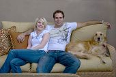 young couple with their dog sitting on couch poster