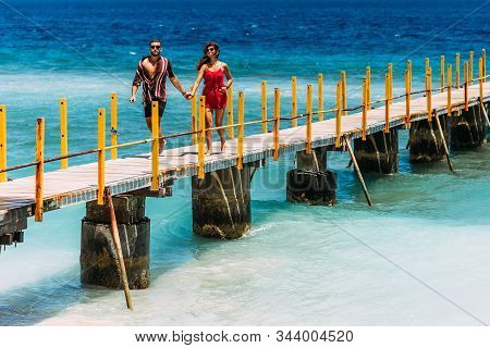 A Couple In Love Holding Hands Runs Along The Pier. Man And Woman Are Resting On The Sea. Beautiful