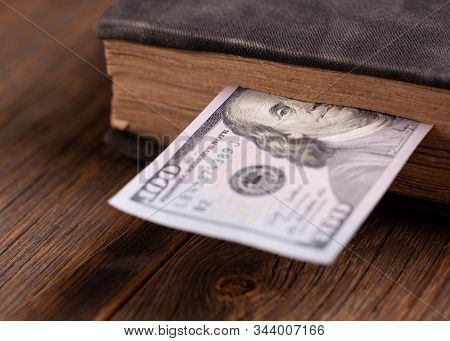 Hundred Dollar Bill Inserted In An Old Book. Hundred Dollar Bill And Book On A Wooden Table. Dollar