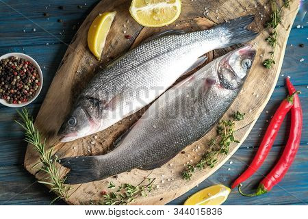 Fresh Seabass And Ingredients For Cooking. Raw Fish Seabass With Lemon, Spices And Herbs On Blue Rus