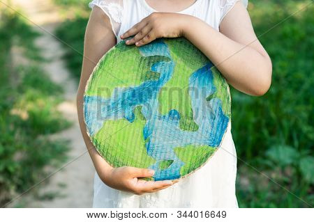 Protection And Love Of Earth. Little Girl Holding Planet In Hands Against Green Spring Background. E
