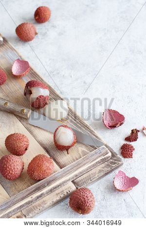 Fresh Litchi Fruits On A Wooden Tray On A White Table