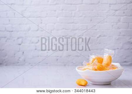 Mangoes Jelly On White Plate And White Brick Wall Texture Background.