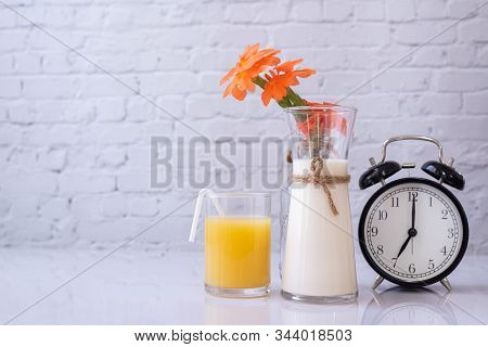Breakfast Table With Glass Of Orange Juice , Bottle Of Milk And Classic Clock.