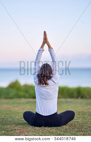 Young beautiful sportwoman practicing yoga. Coach sitting on backview teaching prayer pose at park