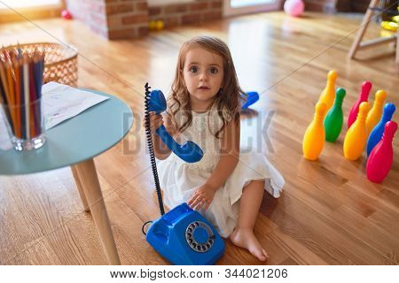 Adorable blonde toddler playing with vintage telephone. Sitting on the floor around lots of toys at kindergarten