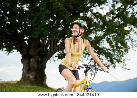 Athlete Happy Girl Cyclist Riding On Yellow Mountain Bike Under Big Tree, Wearing Helmet, Enjoying S