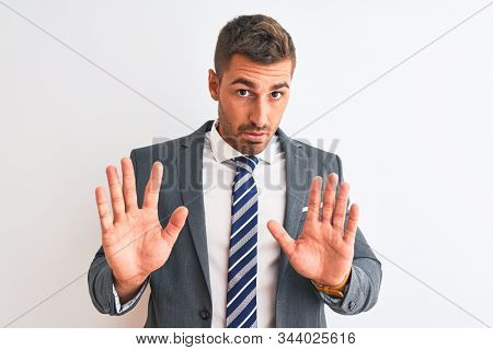 Young handsome business man wearing suit and tie over isolated background Moving away hands palms showing refusal and denial with afraid and disgusting expression. Stop and forbidden.