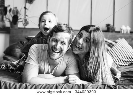 Young Family Having Fun. Together At Home. Happy Childhood. Attractive Young Couple. Parents And Kid