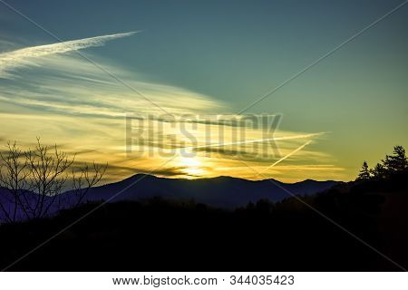 Mountain Silhouette And Contrail During A Sunset In North Carolina