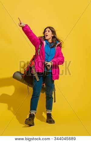 Astonished Pointing Up. Portrait Of A Cheerful Young Caucasian Tourist Girl With Bag And Binoculars