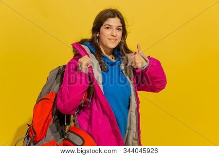 Smiling, Shows Thumb Up. Portrait Of A Cheerful Young Caucasian Tourist Girl With Bag And Binoculars
