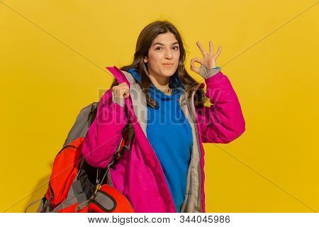 Smiling, Shows Nice. Portrait Of A Cheerful Young Caucasian Tourist Girl With Bag And Binoculars Iso