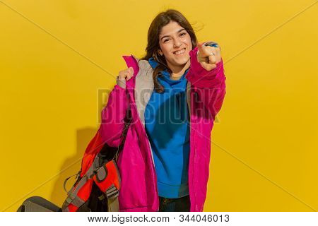 Smiling, Pointing On. Portrait Of A Cheerful Young Caucasian Tourist Girl With Bag And Binoculars Is