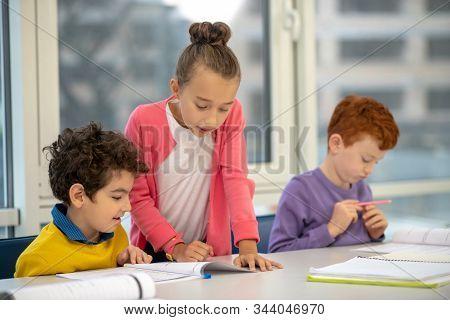 Helpful School Girl Explaining The Task To Classmates