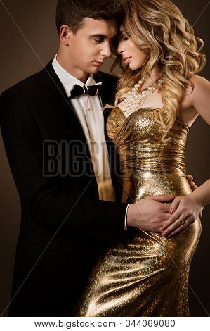 Elegant Couple, Beautiful Fashion Woman In Gold Dress And Man In Tuxedo Suit, Face To Face