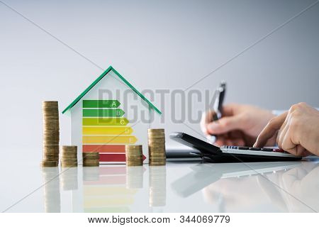 Man Calculating Invoice With Energy Efficient Chart And House
